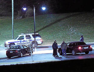 Photo - Police investigate a car, left, at the athletic center of Widener University in Chester, Pa. after a student was shot Monday, Jan. 20, 2014. Authorities warned students to remain indoors until further notice. (AP Photo/Delaware County Daily Times, Robert J. Gurecki)  PHILLY METRO OUT