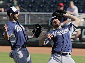 Photo - San Diego Padres first baseman Xavier Nady, right, catches a pop up by Cleveland Indians' Mike Aviles as second baseman Alex Castellanos stands near in the fifth inning of a spring exhibition baseball game Wednesday, March 12, 2014, in Goodyear, Ariz. (AP Photo/Mark Duncan)