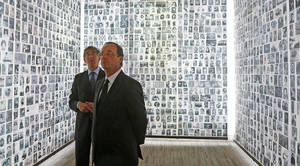 Photo -   Socialist presidential candidate for the upcoming French presidential election Francois Hollande, right, looks at some of the 2,500 photographs of young Jews deported from France during WWII, as he visits the Shoah Memorial in Paris, Sunday, April 29, 2012. (AP Photo/Jacky Naegelen,Pool)