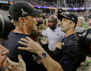 Photo - San Francisco 49ers head coach Jim Harbaugh, left, greets Baltimore Ravens head coach John Harbaugh after the Ravens defeated the 49ers 34-31 in the NFL Super Bowl XLVII football game, Sunday, Feb. 3, 2013, in New Orleans. (AP Photo/Dave Martin)