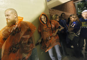Photo - Tim Tandy and Brooke Umholt take cover in the concourse of the stadium as a storm delays the start of the college football game between Tulsa and Oklahoma State Photo by Chris Landsberger, The Oklahoman