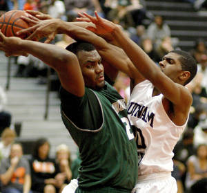 Photo - Edmond Santa Fe's Shaquille Morris, left, gains control of the ball beside Putnam City's Bernard Gainey during a high school basketball game at Putnam City in Oklahoma City, Tuesday, Feb. 7, 2012. Photo by Bryan Terry, The Oklahoman