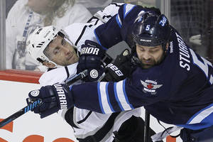 Photo - Winnipeg Jets' Mark Stuart (5) checks Los Angeles Kings' Jarret Stoll (28) during first-period NHL hockey game action in Winnipeg, Manitoba, Thursday, March 6, 2014. (AP Photo/The Canadian Press, John Woods)