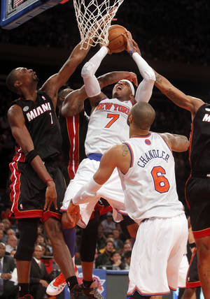 photo -   New York Knicks' Carmelo Anthony (7) shoots against, from left, Miami Heat's Chris Bosh (6), Dwyane Wade (3) and Rashard Lewis (9) during the first half of an NBA basketball game, Friday, Nov. 2, 2012, in New York. (AP Photo/Jason DeCrow)