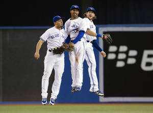 Photo - Toronto Blue Jays' Kevin Pillar, left, Anthony Gose and Colby Rasmus celebrate defeating the New York Yankees during a baseball game in Toronto, Thursday, Sept. 19, 2013. (AP Photo/The Canadian Press, Mark Blinch)