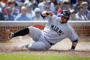 Photo - Miami Marlins' Casey McGehee slides into home on a hit by Jacob Realmuto against the Chicago Cubs during the seventh inning of a baseball game on Sunday, June 8, 2014, in Chicago. (AP Photo/Andrew A. Nelles)