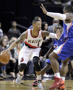 Photo - Portland Trail Blazers guard Damian Lillard, left, looks for room to maneuver around Los Angeles Clippers forward Glen Davis during the first half of an NBA basketball game in Portland, Ore., Wednesday, April 16, 2014. (AP Photo/Don Ryan)