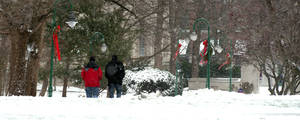 photo - Two people walk through the snow on the Indiana University campus Friday, Dec. 21, 2012 in Bloomington, Ind. The area received about an inch of snow with howling winds through the night.  (AP Photo, Bloomington Herald-Times, David Snodgress)