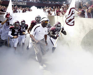 photo -   Texas A&amp;M coach Kevin Sumlin, center, leads his team out onto the field before an NCAA college football game against Florida, Saturday, Sept. 8, 2012, in College Station, Texas. Texas A&amp;M begins a new era with its first Southeastern Conference game after leaving the Big 12 Conference. (AP Photo/David J. Phillip)  