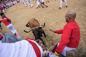 """Photo - Revelers try to protect against a bull on the bull ring, at the San Fermin festival, in Pamplona, Spain, Tuesday, July 8, 2014. Revelers from around the world in Pamplona take part in an eight-day event of the running of the bulls glorified by Ernest Hemingway's 1926 novel """"The Sun Also Rises."""" (AP Photo/Alvaro Barrientos)"""