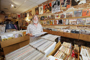 photo - Above: Store owner John Dunning will celebrate his record shop's anniversary Saturday.