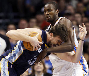 Photo - Oklahoma City's Serge Ibaka (9) defends Memphis' Marc Gasol (33) during the NBA basketball game between the Memphis Grizzlies and the Oklahoma City Thunder at Chesapeake Energy Arena in Oklahoma City, Monday, April 2, 2012. Photo by Nate Billings, The Oklahoman
