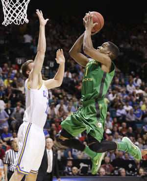Photo - Oregon's Dominic Artis shoots against UCLA's David Wear in the first half of the NCAA college basketball game in the Pac-12 Conference tournament Saturday, March 16, 2013, in Las Vegas. (AP Photo/Julie Jacobson)  ORG XMIT: NVJJ125