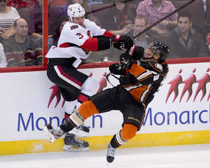 Photo - Ottawa Senators defenseman Marc Methot collides with Anaheim Ducks left wing Jakob Silfverberg along the boards during the second period of an NHL hokey game,  Friday Oct. 25, 2013 in Ottawa, Ontario. (AP Photo/The Canadian Press, Adrian Wyld)