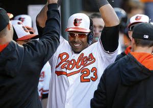 Photo - Baltimore Orioles' Nelson Cruz high-fives teammates in the dugout after hitting a solo home run in the seventh inning of an opening day baseball game against the Boston Red Sox, Monday, March 31, 2014, in Baltimore. Baltimore won 2-1. (AP Photo/Patrick Semansky)