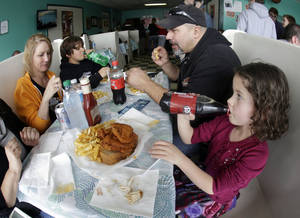 Photo - In this Friday, March 23, 2013 photo, Madison Lehman, 5, right, takes a drink after tasting her first piece of hot chicken at Prince's Hot Chicken Shack in Nashville, Tenn. Hot chicken -- fried chicken with varied amounts of seasoning that make the heat level run from mild to extra hot -- is a signature dish of Nashville. Also shown are Cherie Salazar, left, Joey Lehman, 11, and Manny Salazar. (AP Photo/Mark Humphrey)