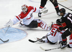 Photo - Austria goaltender Bernhard Starkbaum reaches back as the puck shot by Canada forward Jeff Carter, flies into the net for a goal in the second period of a men's ice hockey game at the 2014 Winter Olympics, Friday, Feb. 14, 2014, in Sochi, Russia. (AP Photo/Julio Cortez)