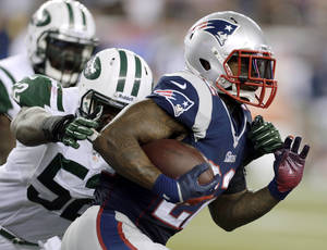 Photo - New England Patriots running back Stevan Ridley (22) runs past New York Jets inside linebacker David Harris (52) during the first half of an NFL football game Thursday, Sept. 12, 2013, in Foxborough, Mass. (AP Photo/Charles Krupa)