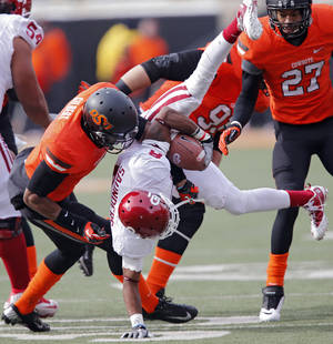 Photo - Oklahoma State's Justin Gilbert (4) upends Oklahoma's Jalen Saunders (8) during the Bedlam college football game between the Oklahoma State University Cowboys (OSU) and the University of Oklahoma Sooners (OU) at Boone Pickens Stadium in Stillwater, Okla., Saturday, Dec. 7, 2013. Photo by Chris Landsberger, The Oklahoman