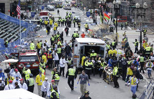 Photo - Medical workers aid injured people on April 15 following an explosion at the finish line of the 2013 Boston Marathon in Boston. U.S. Attorney General Eric Holder said Thursday that officials would seek the death penalty against bombing suspect Dzhokhar Tsarnaev. AP FILE PHOTO