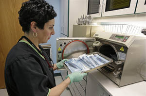 "Photo - Dentist Alice G. Boghosian removes packages of properly sterilized dental instruments from an autoclave that uses heat and steam to sterilize the tools Friday, March 29, 2013, in Chicago. Health officials in Oklahoma are calling an oral surgeon there who used dirty equipment and risked cross-contamination a ""menace to public health"" and are urging thousands of his patients to seek medical screenings for hepatitis B, hepatitis C and HIV. Though officials say such situations involving dental clinics are rare, Dr. Matt Messina, a dentist in Cleveland, and a consumer advisor for the American Dental Association, says patients should ask their dentist and oral surgeon about the steps they and their staffs take to sterilize equipment. (AP Photo/M. Spencer Green)"