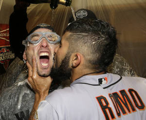 Photo -   Sergio Romo kisses Marco Scutaro as they are sprayed with champagne in the locker room as San Francisco Giants celebrate after the Giants defeated the Detroit Tigers, 4-3, in Game 4 of baseball's World Series Sunday, Oct. 28, 2012, in Detroit. The Giants won the World Series 4-0. (AP Photo/David J. Phillip)