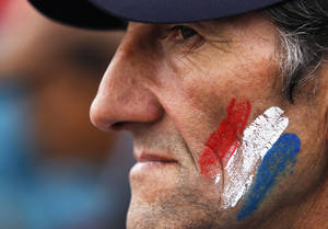 Photo -   A supporter of Paraguay's President Fernando Lugo, whose face is painted with the colors of Paraguay's national flag, stands outside Parliament, in Plaza de Armas, where a large group gathered to protest against Lugo's impeachment trial, Asuncion, Paraguay, Friday, June 22, 2012. Paraguayan lawmakers voted Thursday to impeach Lugo for his role in a deadly clash involving landless farmers and police. Lugo's trial was to begin Friday in Paraguay's Senate. (AP Photo/Jorge Saenz)