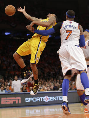 Photo - New York Knicks forward Carmelo Anthony (7) fouls Indiana Pacers guard George Hill (3) in the second quarter of Game 1 of their second-round NBA basketball series at Madison Square Garden in New York, Sunday, May 5, 2013.  (AP Photo/Kathy Willens)