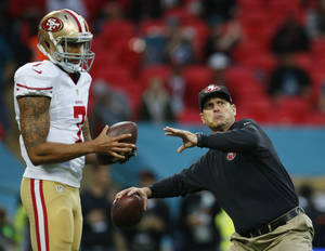 Photo - San Francisco 49ers quarterback Colin Kaepernick, left, watches as 49ers head coach Jim Harbaugh throws a football before the NFL football game against the Jacksonville Jaguars at Wembley Stadium, London, Sunday, Oct. 27, 2013.  (AP Photo/Matt Dunham)
