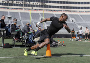 Photo - OSU's Joseph Randle rounds a cone as part of an agility test during Pro Day at Boone Pickens Stadium on the campus of Oklahoma State University in Stillwater, OK, Tuesday, March 12, 2013,  By Paul Hellstern, The Oklahoman