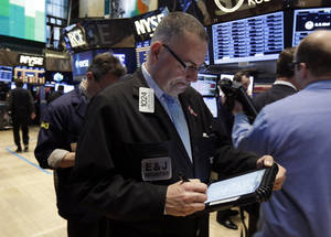 Photo - Trader John Yaccarine, center, works on the floor of the New York Stock Exchange Wednesday, March 19, 2014. Stocks are slightly lower in early trading on Wall Street as traders wait for the latest policy decision from the Federal Reserve. (AP Photo/Richard Drew)