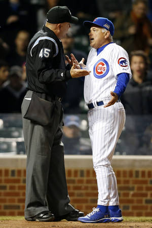 Photo - Umpire Jeff Nelson and Chicago Cubs manager Rick Renteria argue a call during the ninth inning of a baseball game against the Pittsburgh Pirates on Tuesday, April 8, 2014, in Chicago. Chicago Cubs manager Rick Renteria was ejected from the game following the argument. The Pittsburgh Pirates won 7-6. (AP Photo/Andrew A. Nelles)
