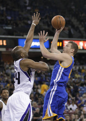 Photo - Golden State Warriors forward David Lee, right, shoots over Sacramento Kings forward Carl Landry during the first quarter of an NBA basketball game in Sacramento, Calif., Wednesday, Feb. 19, 2014. (AP Photo/Rich Pedroncelli0