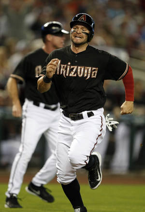 Photo - Arizona Diamondbacks left fielder Cody Ross scores after a misplayed ball by San Diego Padres third baseman Chase Headley in the first inning of a baseball game, Monday, May 26, 2014, in Phoenix. (AP Photo/Rick Scuteri)