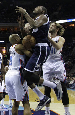 Photo - Oklahoma City Thunder's Kevin Durant, center, is fouled as he drives between Charlotte Bobcats' Gerald Henderson, left, and Josh McRoberts during the first half of an NBA basketball game in Charlotte, N.C., Friday, Dec. 27, 2013. (AP Photo/Chuck Burton)