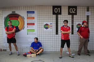 Photo - In this  June 18, 2014, photo, Chilean supporters wait for ticket sellers before the starting of the group B World Cup soccer match between Spain and Chile at the Maracana Stadium in Rio de Janeiro, Brazil, Wednesday. Selling tickets to sporting events for prices higher than face value is a crime in Brazil punishable by up to, two years in prison. Accused scalpers are taken to police stations and released after signing a document pledging to show up for a court date. (AP Photo/Bernat Armangue)