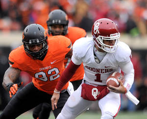 Photo - Oklahoma State defensive end Jimmy Bean, left, reaches for Oklahoma quarterback Kendal Thompson during the first half of an NCAA football game in Stillwater, Okla., Saturday, Dec. 7, 2013. Thompson had 17 yards passing in the 33-24 win over rival Oklahoma State. (AP Photo/Brody Schmidt)