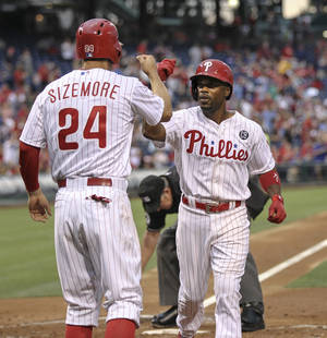 Photo - Philadelphia Phillies' Grady Sizemore, left, greets Jimmy Rollins at home plate after his two-run home run against the Washington Nationals during the third inning of a baseball game in Philadelphia, Friday, July 11, 2014. (AP Photo/Philadelphia Daily News, Steven M. Falk)