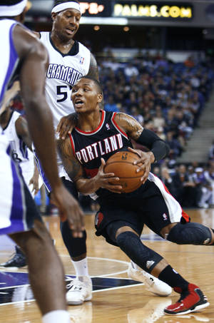 photo - Portland Trail Blazers guard Damian Lillard, right, drives to the basket around Sacramento Kings defender James Johnson during the first half of an NBA basketball game in Sacramento, Calif., on Sunday, Dec. 23, 2012. (AP Photo/Steve Yeater)