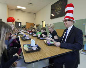 Photo - Edmond Public Schools Superintendent David Goin eats green eggs and ham with first-graders at Clegern Elementary School in honor of Dr. Seuss' birthday. PHOTO BY PAUL HELLSTERN, THE OKLAHOMAN. <strong>PAUL HELLSTERN - Oklahoman</strong>
