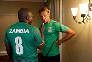 photo - Zambia's head coach Herve Renard, from France, right, is interviewed by a journalist wearing a team shirt at a hotel in Nelspruit, South Africa, Thursday, Jan. 24 2013. Zambia will play Nigeria in a African Cup of Nations group C match on Friday. The two other teams in group C are Ethiopia and Burkina Faso. (AP Photo/Armando Franca)