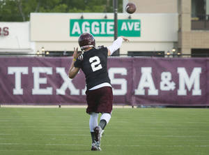 Photo - Texas A&M quarterback Johnny Manziel warms up with teammates on the first day of fall practice in College Station, Texas, Monday, Aug. 5, 2013.  (AP Photo/Bryan College Station Eagle, Stuart Villanueva)