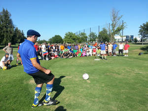 Photo - A footgolf player kicks a ball toward the hole.  Photo provided <strong></strong>