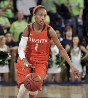 Photo - Miami guard Caprice Dennis heads up court during the first half of an NCAA college basketball game with Notre Dame, Thursday, Jan. 23, 2014 in South Bend, Ind. (AP Photo/Joe Raymond)
