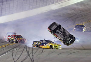 Photo - Clint Bowyer's car (15) becomes airborne after being hit by David Ragan (34) during the second of two NASCAR Sprint Cup series qualifying auto races at Daytona International Speedway in Daytona Beach, Fla., Thursday, Feb. 20, 2014. (AP Photo/David Graham)