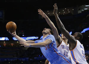 Photo - Los Angeles Clippers forward Blake Griffin (32) drives between Oklahoma City Thunder center Steven Adams (12) and forward Serge Ibaka (9) in the first quarter of an NBA basketball game, Sunday, Feb. 23, 2014, in Oklahoma City. (AP Photo/Sue Ogrocki)