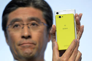 Photo - Kunimasa Suzuki, executive vice president, Sony Corporation and president and chief executive officer of Sony Mobile Communications, unveils the new Sony EXPERIA Z1 Compact during the Sony news conference at the International Consumer Electronics Show Monday, Jan. 6, 2014, in Las Vegas. The smaller phone has the same features as the ZPERIA Z1(AP Photo/Jack Dempsey)