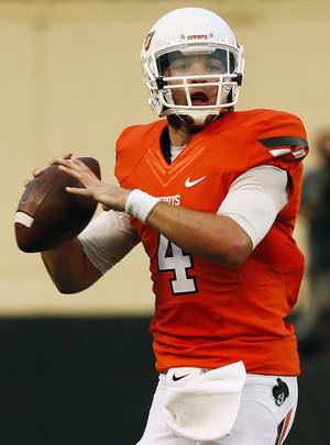 Photo - Oklahoma State's J.W. Walsh (4) looks to pass during a college football game between the Oklahoma State University Cowboys (OSU) and the Lamar University Cardinals at Boone Pickens Stadium in Stillwater, Okla., Saturday, Sept. 14, 2013. Photo by Nate Billings, The Oklahoman