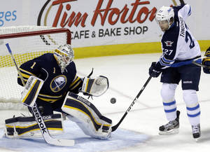 Photo - Buffalo Sabres goalie Jhonas Enroth of Sweden makes a save on a shot by Winnipeg Jets' Eric Tangradi (27) during the first period of an NHL hockey game in Buffalo, N.Y., Monday, April 22, 2013. (AP Photo/David Duprey)