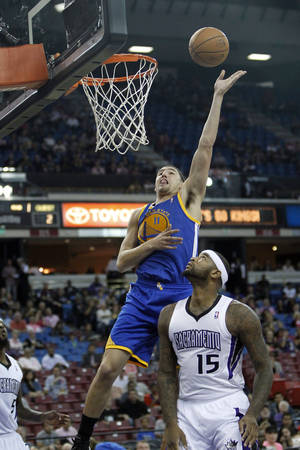 Photo - Golden State Warriors guard Klay Thompson, top, goes to the basket against Sacramento Kings center DeMarcus Cousins during the first quarter of an NBA preseason basketball game in Sacramento, Calif., Wednesday, Oct. 23, 2013. (AP Photo/Rich Pedroncelli)